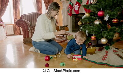 Young woman decorating Christmas tree with her baby son