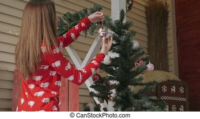 Young woman decorating Christmas tree with red balls at home