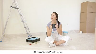 Young woman decorating her new house relaxing on the floor...
