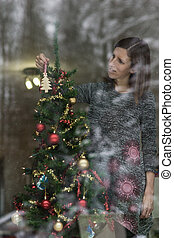 Young woman decorating holiday tree