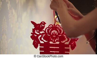 Young woman decorating room with chinese symbol