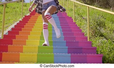 Young woman descending rainbow colored steps - Young woman...