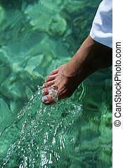 Young woman dipping toes in water