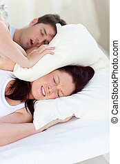 Young woman disturbed by the snores of her boyfriend in the...