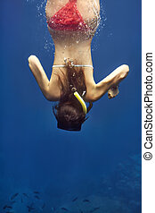 Young woman dives in tropical sea
