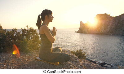 Young woman do yoga at the cliff