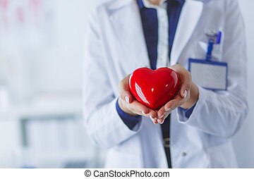 Young woman doctor holding a red heart, standing on hospital background