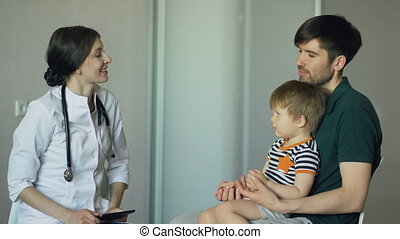 Young woman doctor talking with father of little boy in medical office