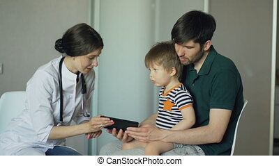 Young woman doctor talking with father of little boy using tablet computer in medical office