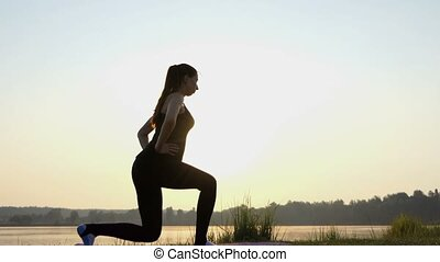 Young Woman Does a Split Squat And a Lunge at Sunset in 4k
