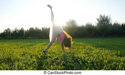 Young woman doing a handstand at sunset meadow outdoors
