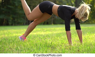young woman doing a sport exercise outdoors