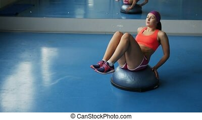 Young woman doing abdominal exercises at sport gym.