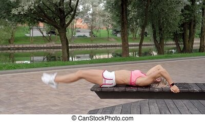 Young woman doing abs crunches in park on a bench