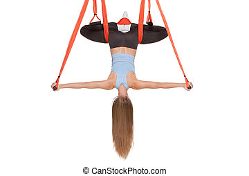 Young woman doing anti-gravity aerial yoga in hammock on a...