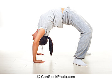 Young woman doing back bend on floor over white background