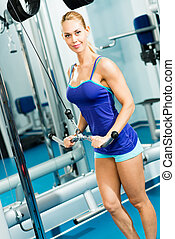 young woman doing body-building in the Gym