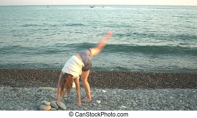 Young woman doing cartwheel on beach at sunset Summer