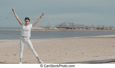 young woman doing Cartwheel on the beach at summer