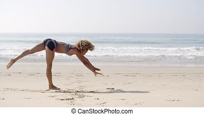 Young Woman Doing Cartwheel On The Beach - Young woman doing...
