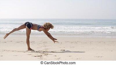 Young Woman Doing Cartwheel On The Beach - Young woman doing...