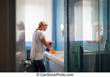 Young woman doing chores and cleaning bathroom at home