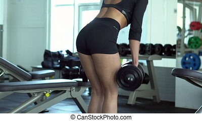 young woman doing deadlifts with dumbbells in the gym