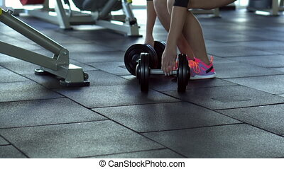 young woman doing deadlifts with dumbbells in the gym -...