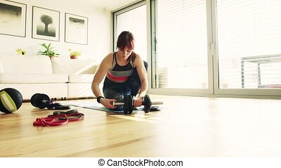 Young woman doing exercise at home.