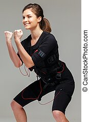 Young woman doing exercise in Electro Muscular Stimulation ...