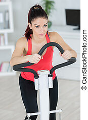 young woman doing exercise on bicycle at home