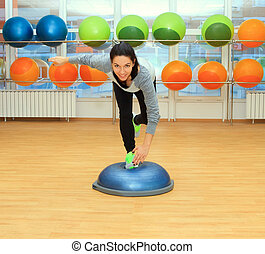 Young woman doing exercise on bosu ball