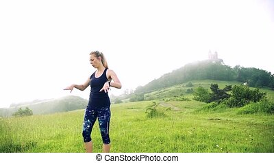 A young woman doing exercise on meadow outdoors in nature early in the morning. Slow motion.