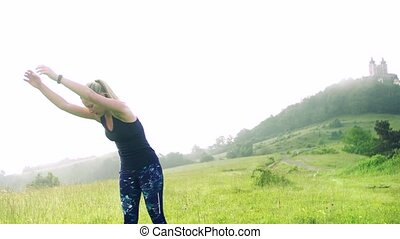 A young woman doing exercise on meadow outdoors in nature early in the morning.