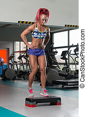 Young Woman Doing Exercise On Stepper In Gym - Young Woman...