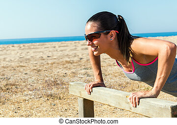 Young woman doing exercise on wooden structure.