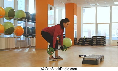 Young woman doing exercise with bar