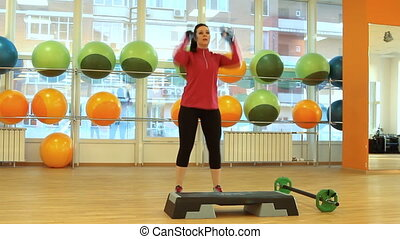 Young woman doing exercise with dum