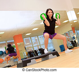 Young woman doing exercise with dumbbells