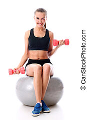 Young woman doing exercise with dumbells on a ball