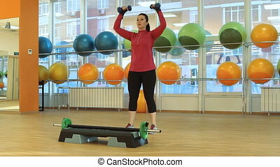 Young woman doing exercise with dumbells