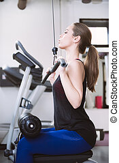 Young woman doing exercises on a machine at the gym