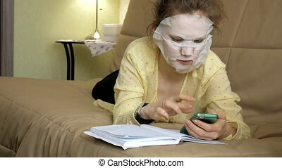Young woman doing facial mask mask with cleansing mask,...