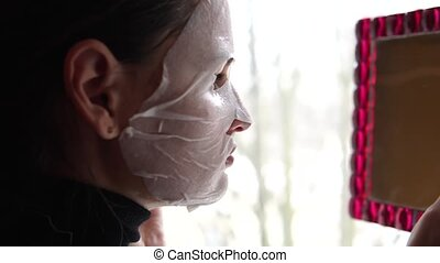 Young woman doing facial mask sheet with purifying mask on her face.