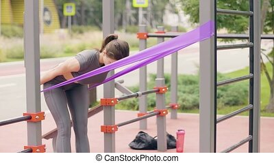 Young woman doing fitness exercise with sport expander on sports ground