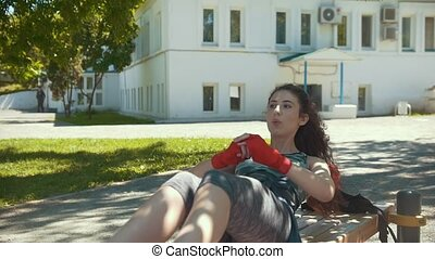 Young woman doing fitness exercises outdoors at sunny day