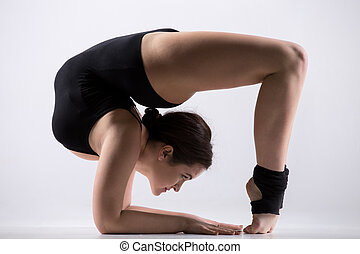 Young woman doing gymnastics backbend pose