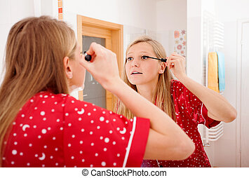 Young woman doing her make up - Young woman putting mascara...