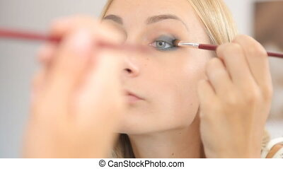 Young woman doing makeup in front of a mirror, full face, blurred background.