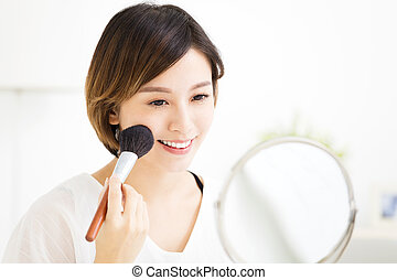 young woman doing makeup in front of the mirror